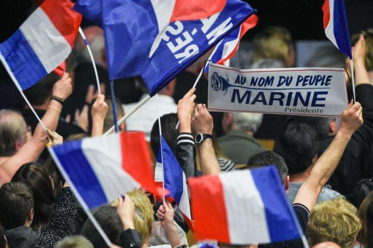 Supporters wave French flags during a rally of French presidential election candidate for the far-right Front National (FN) party Marine Le Pen, in Monswiller, north-eastern France, on April 5, 2017