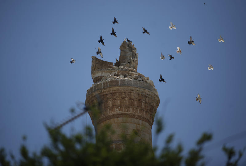 FILE - In this Sunday, June 10, 2012 file photo, birds fly over a destroyed minaret of a mosque at the northern town of Ariha, on the outskirts of Idlib, Syria. During two weeks with rebels in northern Syria, three Associated Press journalists found more than 20 rebel groups who often destroy government army posts and convoys but lack the weapons and unity to do more than gradually chip away at the regime of President Bashar Assad _ a recipe for a long, bloody insurgency.(AP Photo/Khalil Hamra, File)
