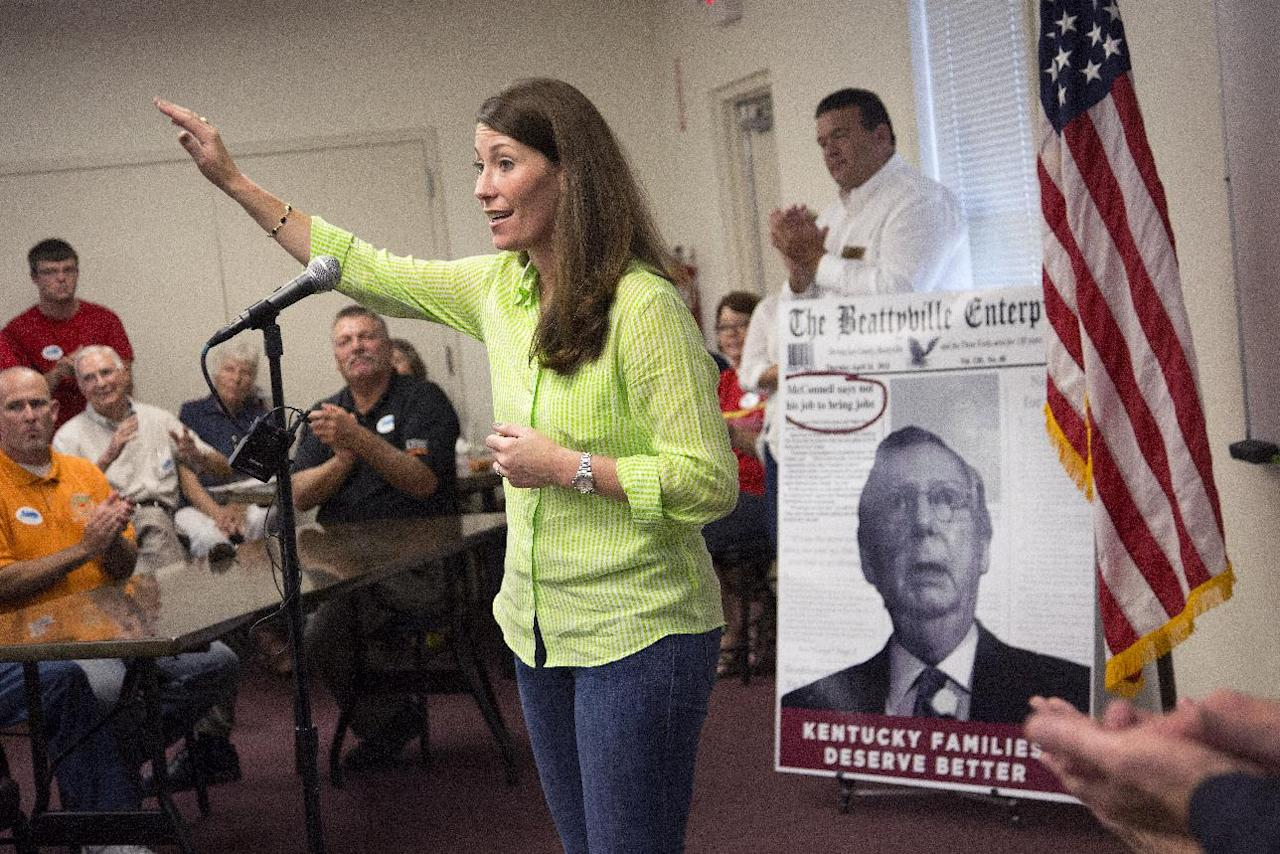 FILE - This July 30, 2014, file photo shows U.S. Senate candidate and Kentucky Secretary of State Alison Lundergan Grimes (D-KY), as she speaks to supporters in Hawesville, Ky., as a poster of her rival Senate Minority Leader Mitch McConnell of Ky., serves as a backdrop. The annual picnic at Fancy Farm always serves up a main dish of politics along with a side of delicious barbecue. And on Aug. 2, 2014, voters will get a rare glimpse of Kentucky's U.S. Senate candidates standing side by side as they face armies of hecklers trying to spook them off their talking points. McConnell and his Democratic challenger, Grimes, will share the same stage for only the second time.(AP Photo/David Stephenson, File)