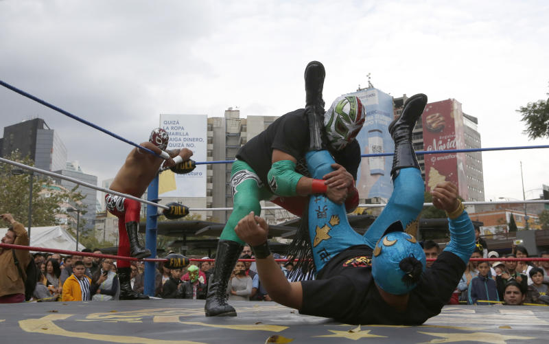 """Mexican wrestler Rakner clashes with Relampago Veloz during """"lucha libre"""" fight in Mexico City, Saturday, Dec. 21, 2019. Mexican wrestling, otherwise known as the """"lucha libre,""""  is a highly traditional form of light entertainment. (AP Photo/Ginnette Riquelme)"""