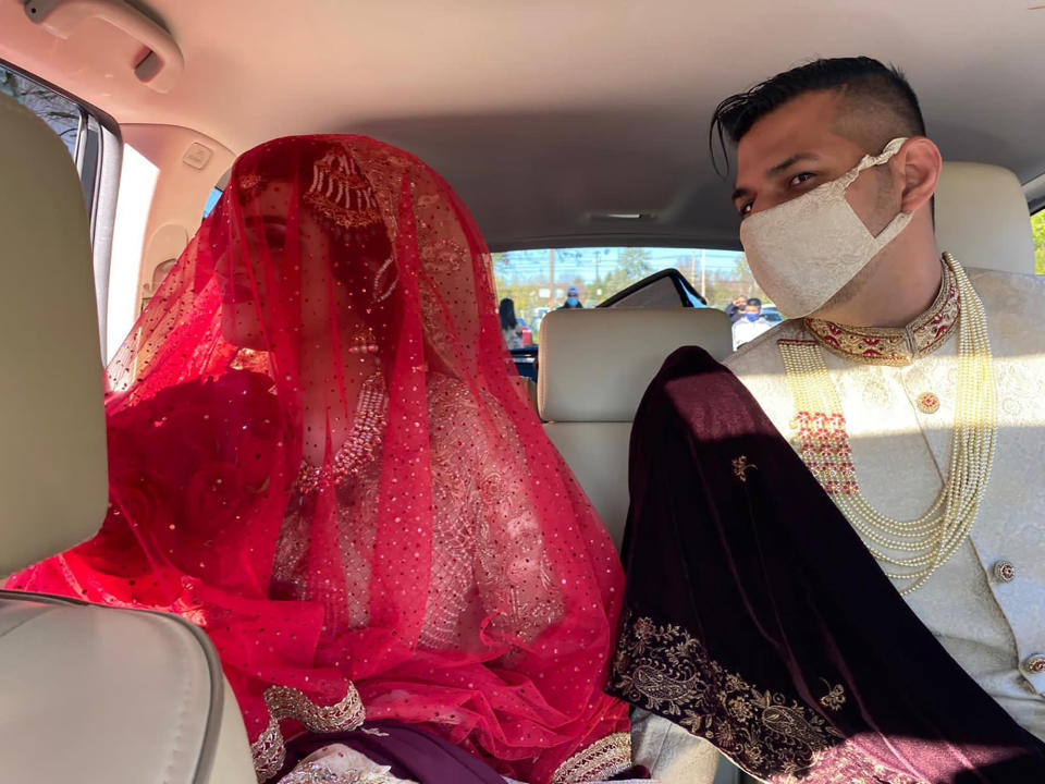 """Jumana Azam and her husband, Shafaq Ahmed drive off after their small wedding ceremony in Parsippany-Troy Hills, N.J., on Oct. 31, 2020. For a time this past spring, Azam, a respiratory therapist, was working 16-hour days responding to an influx of coronavirus patients at Chicago's Rush University Medical Center. Her hours have decreased since then, and the couple decided to set their wedding date for October. """"If you surround yourself with love and happiness, good things will still happen in a terrible year,"""" said Azam. (Nada Gomaa via AP)"""