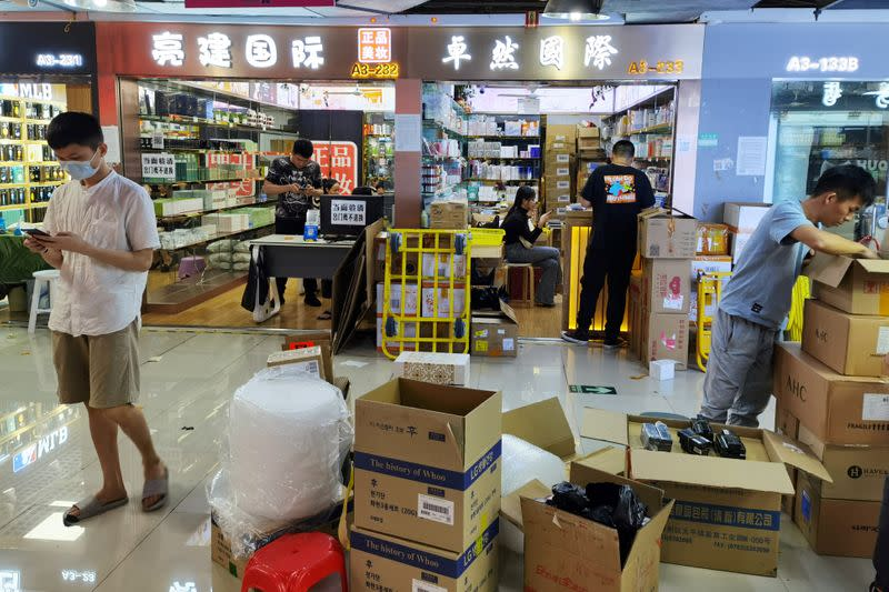 Boxes of cosmetics are unloaded at the Mingtong Digital City market in Shenzhen's Huaqiangbei area