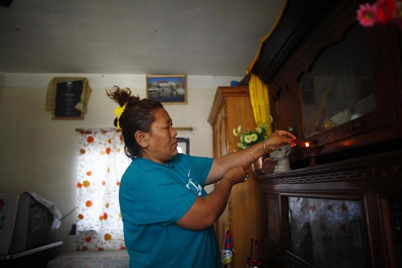 In this Wednesday, April 2, 2014 photo, a Tibetan refugee Sonam Chodon lights incense sticks inside her home at the Tibetan refugee camp in Katmandu, Nepal. Chodon said she and another Tibetan Sonam Tashi were held for weeks after being picked up by police who broke up a small rally in front of the Chinese Embassy visa office on March 10 and were released only this week without charges or access to legal aid in a sign that authorities are bowing to pressure from China. The government on Thursday denied accusations in a report by Human Rights Watch that it is mistreating Tibetans. Nearly 20,000 Tibetans who fled their homeland now live in Nepal. (AP Photo/Niranjan Shrestha)