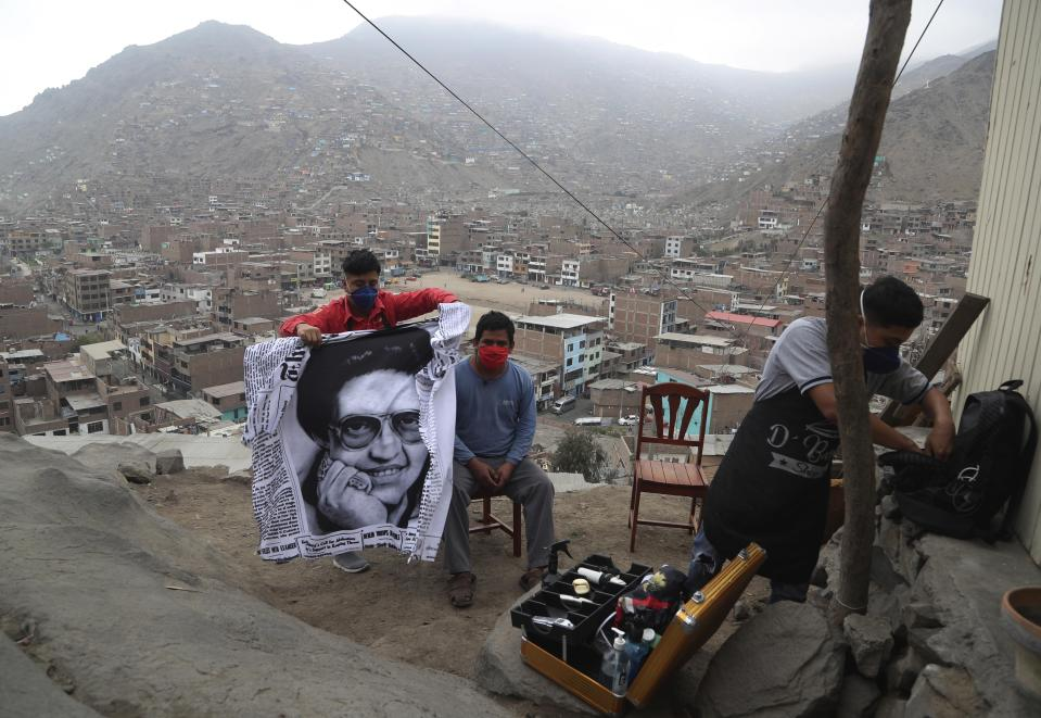 "Josue Yacahuanca, a 21-year-old barber, puts an apron emblazoned with an image of salsa singer Hector Lavoe on a resident as he prepares to give him a free haircut, in the San Juan de Lurigancho neighborhood of Lima, Peru, Friday, June 19, 2020. Greeting each client, Yacahuanca drapes his clients with the apron, bringing with him memories of the music he always had playing in his shop. ""I'm a fan of his music,"" Yacahuanca said. ""He sings about the realities of life - sadness and joy."" (AP Photo/Martin Mejia)"