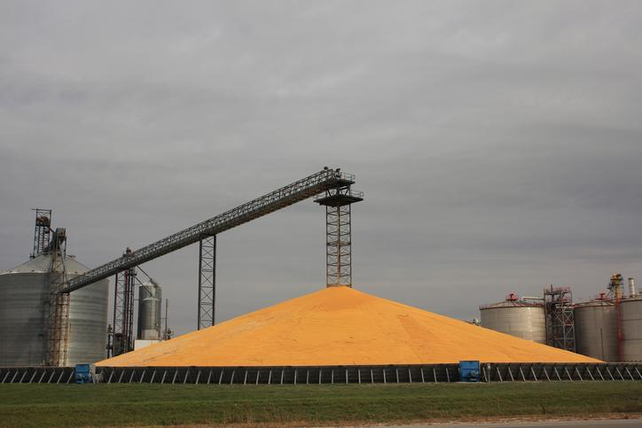 A giant pile of corn kernels next to a grain storage facility.