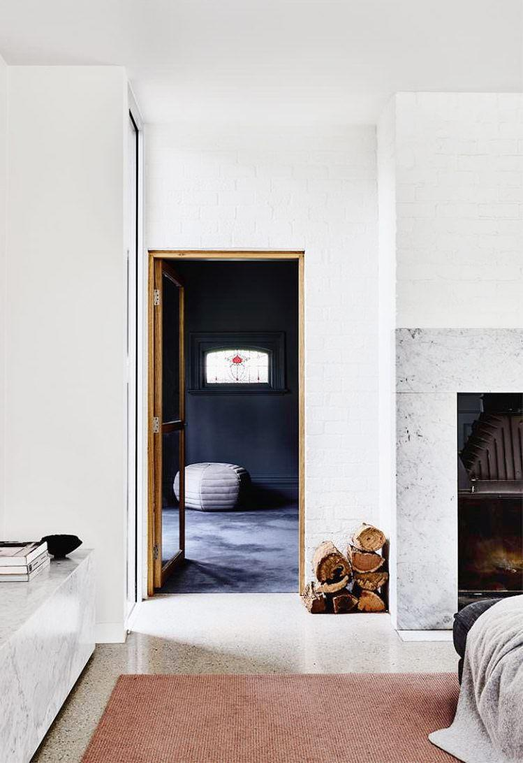 <p>A black box theater effect frames the stained glass details in the window beyond. Fiona Lynch distinguishes the media room from the adjacent bright white living room with an inky color scheme and plush, rich gray carpeting for optimal comfort. </p>