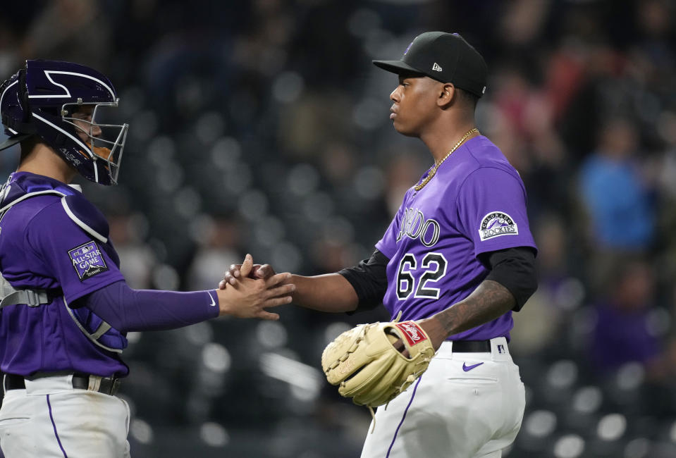 Colorado Rockies catcher Dom Nunez, left, congratulates relief pitcher Yency Almonte after he retired the Arizona Diamondbacks in the ninth inning of a baseball game Friday, May 21, 2021, in Denver. (AP Photo/David Zalubowski)