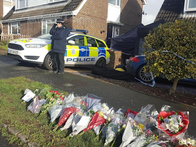 Police stand guard over tributes at the scene of the double murder. (PA)