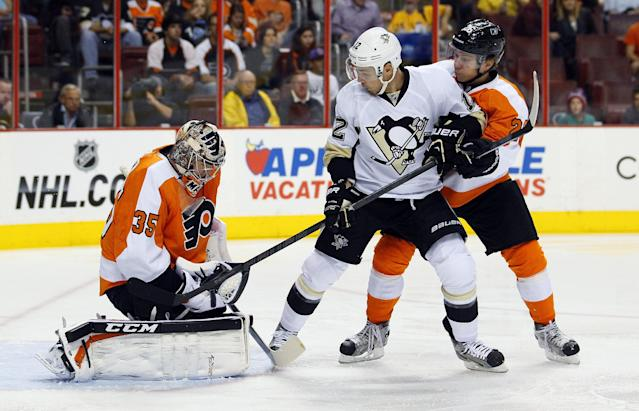 Philadelphia Flyers goalie Steve Mason, left, holds on to the puck as Pittsburgh Penguins' Chuck Kobasew, center, and Flyers' Claude Giroux, right, watch in the first period of an NHL hockey game, Thursday, Oct. 17, 2013, in Philadelphia. (AP Photo/Tom Mihalek)