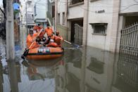 National Disaster Response Force (NDRF) personnel evacuate local residents in a boat along a flooded street following heavy rains in Hyderabad on October 15, 2020. (Photo by NOAH SEELAM / AFP) (Photo by NOAH SEELAM/AFP via Getty Images)