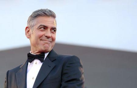 "U.S. actor Clooney smiles as he arrives on the red carpet for the premiere of ""Gravity"" at the 70th Venice Film Festival in Venice"