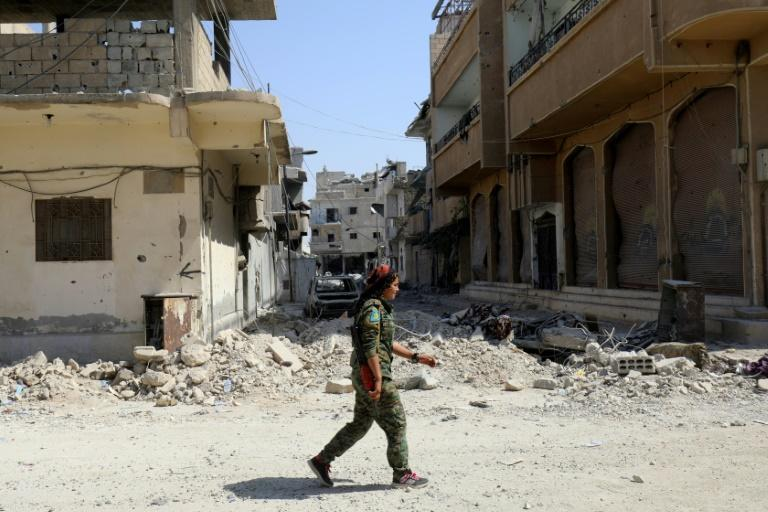 A member of the Syrian Democratic Forces walks in the former Islamic State group stronghold of Raqa on September 21, 2017