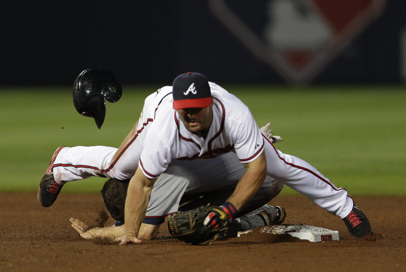 Minnesota Twins' Trevor Plouffe (24) is forced out at second base by Atlanta Braves second baseman Dan Uggla (26) on a Ryan Doumit (9) ground ball in the ninth inning of a baseball game Tuesday, May 21, 2013 in Atlanta. Plouffe was injured on the play and left the field under his own power. Atlanta won 5-4 in ten innings. (AP Photo/John Bazemore)