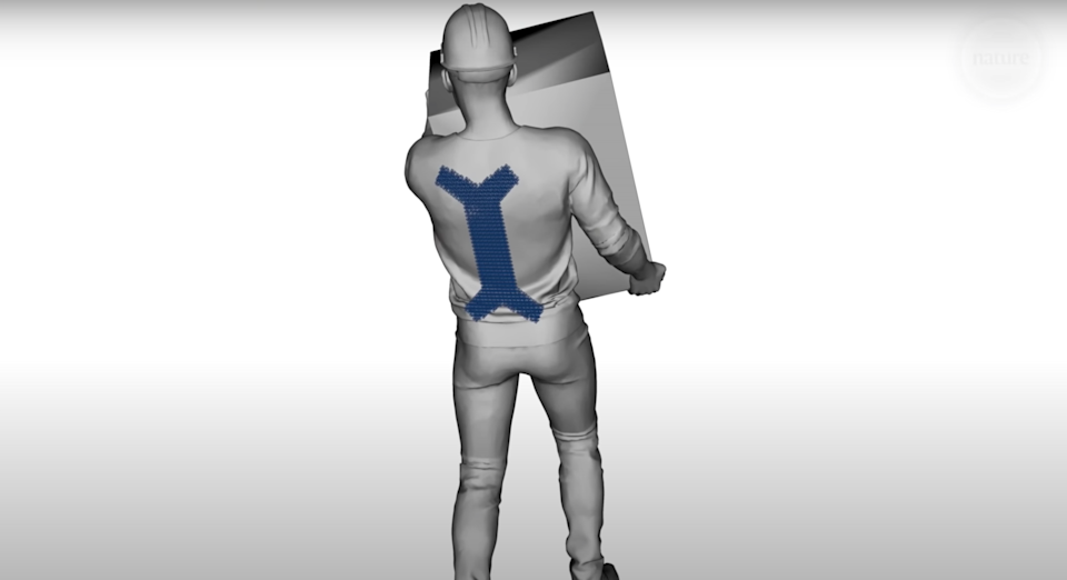 A digital illustration of a worker carrying a box, aided by a small, chain mail exoskeleton on his back.