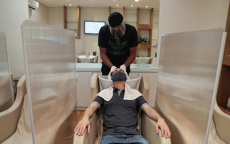 A hairdresser wearing protective mask and face shield dries customer's hair between acrylic walls set up for social distancing - AMANDA PEROBELLI/Reuters