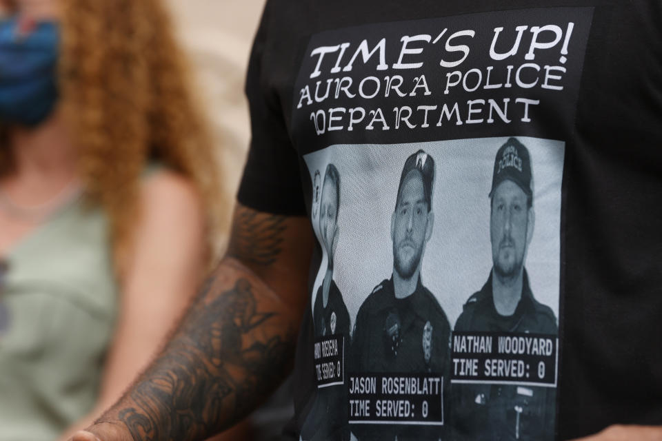 At a news conference in Aurora, Colo. in July 2020, a protester wears a shirt with photographs of the police officers involved in the fatal encounter with Elijah McClain.