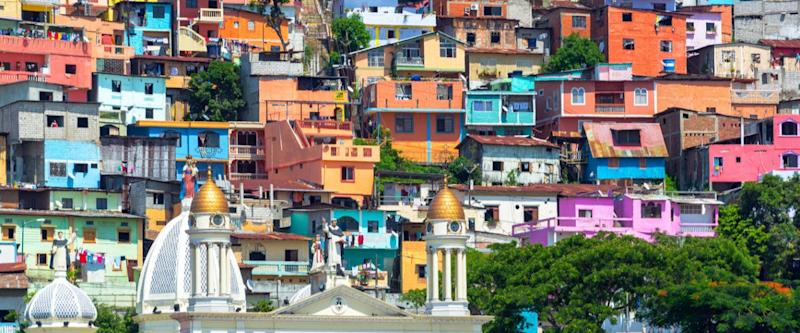 White church with a colorful slum on a hill rising above it in Guayaquil, Ecuador