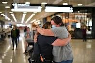 A mother (R) embraces her daughter upon her arrival from New Zealand at Sydney International Airport