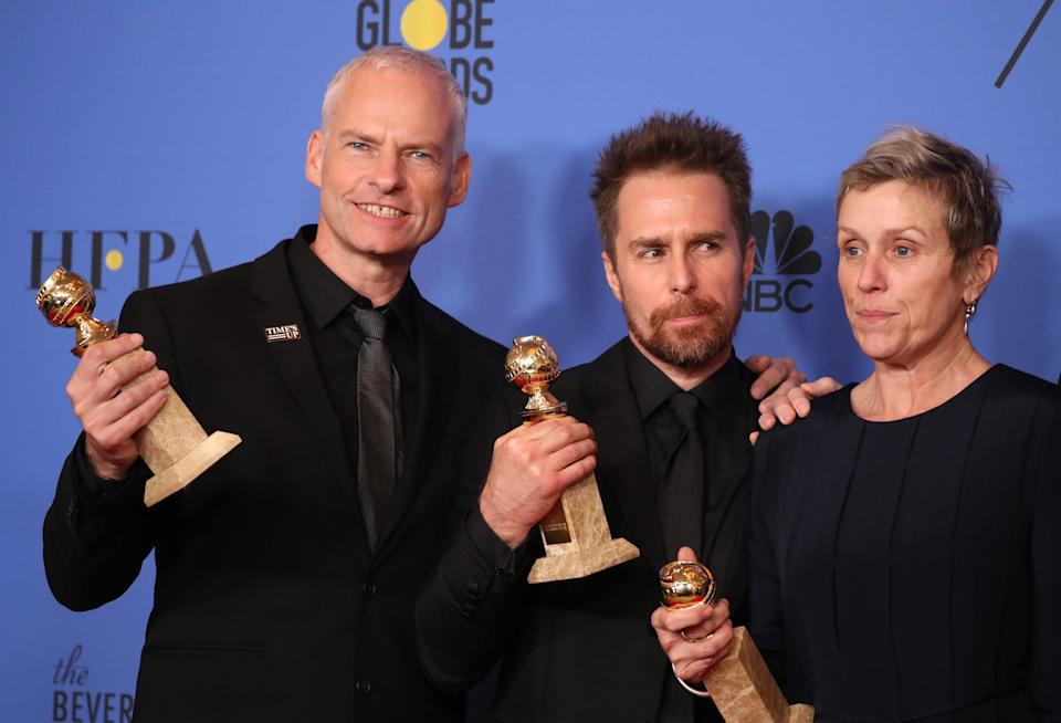 """Martin McDonagh (L), winner for Best Screenplay – Motion Picture, Sam Rockwell, winner for Best Performance By An Actor In A Supporting Role In Any Motion Picture, and Frances McDormand, winner for Best Performance By An Actress In A Motion Picture – Drama, pose backstage after also winning the award for Best Motion Picture – Drama for """"Three Billboards Outside Ebbing, Missouri."""" REUTERS/Lucy Nicholson"""
