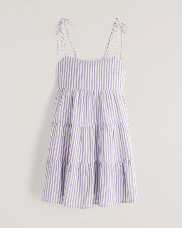 """<p><strong>Abercrombie & Fitch Tie-strap Tiered Mini Dress in White Stripe, $69, <a href=""""https://rstyle.me/+OIkEQKCfZPEzqGrMAdvOOg"""" rel=""""nofollow noopener"""" target=""""_blank"""" data-ylk=""""slk:available here"""" class=""""link rapid-noclick-resp"""">available here</a> (sizes XXS-XL):</strong> """"If you had told me in 2021 I love Abercrombie's simple dresses for just throwing into my bag and going, I would not believe you, but here we are. I especially love that they come in 'tall' lengths."""" —Liza Sokol, Senior Audience Development Manager </p>"""