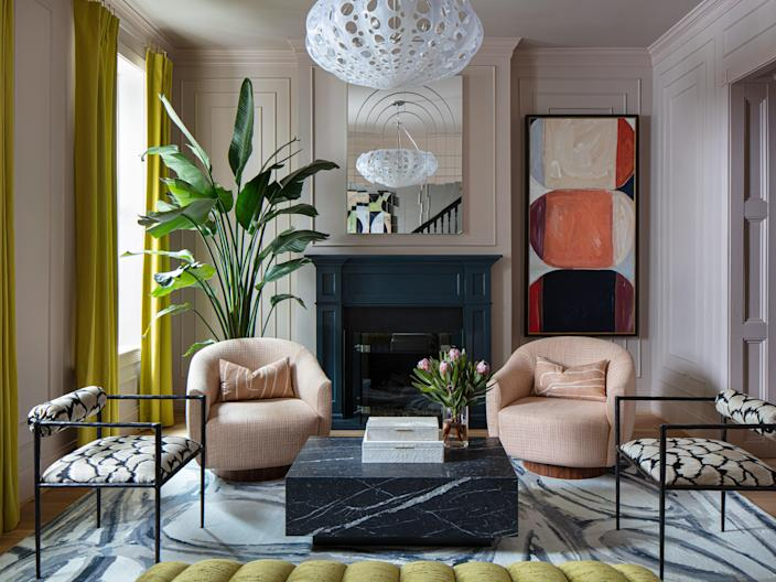 """Lindsay Cowles put on her artist hat to create a custom pale pink paint for her front parlor walls by combining two Farrow & Ball colors. """"It couldn't be too beige or too purple,"""" she says. """"It had to have the right amount of gray. It was really tricky."""" Jill designed the living room around Lindsay's Blue Grey Rug, layering in chartreuse draperies, Kelly Wearstler swivel chairs, Oly Studio lighting, pattered armchairs, a custom mirror, and one of Lindsay's abstract paintings."""