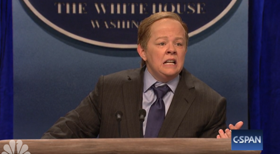 Melissa McCarthy, as Sean Spicer, rides her podium through NY