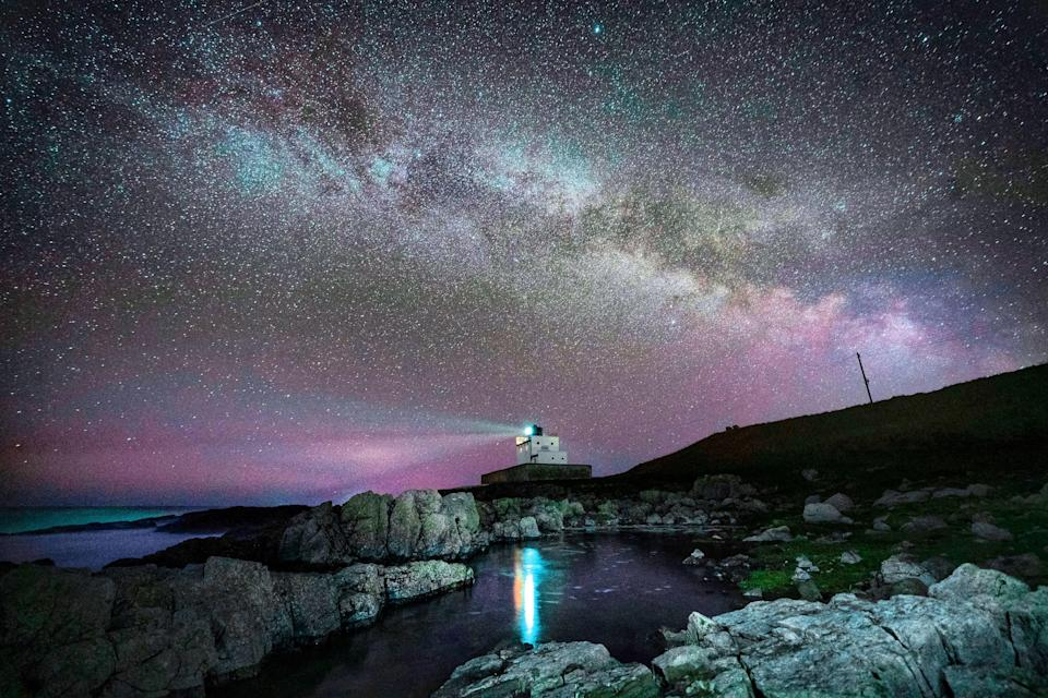 The core of the Milky Way becomes visible in the early hours of Tuesday morning as it moves over Bamburgh Lighthouse at stag Rock in Northumberland (PA)