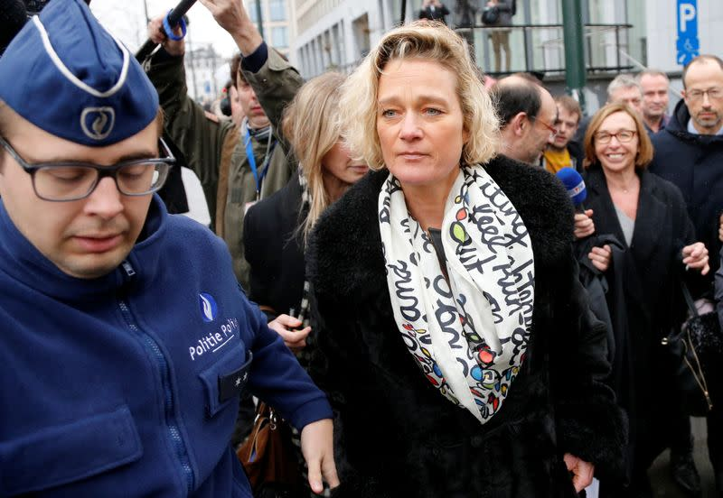 Belgian artist Boel is escorted by police officers as she leaves a courthouse in Brussels