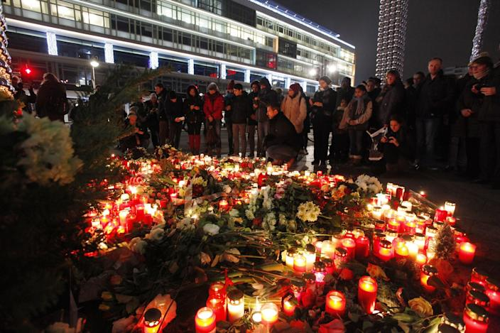 People leave flowers and candles at the site in Berlin where a truck plowed through a Christmas market, killing 12 people and wounding 50 others. (Photo: Michele Tantussi/Getty Images)
