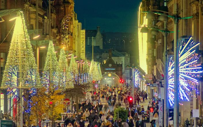 The city Christmas lights where switched on without fanfare or crowds as the civic centre of George Square and the style mile of Scotland saw shoppers and tourists ahead of the city entering Tier 4 lockdown restrictions - Alamy Live News
