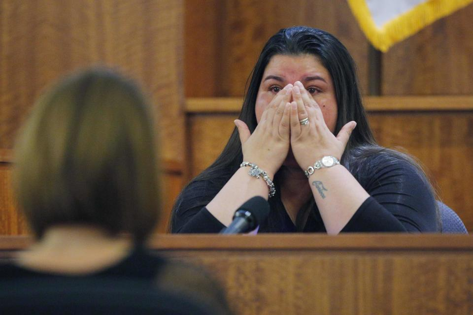 House cleaner Carla Barbosa wipes her face, while testifying in the murder trial of former New England Patriots player Aaron Hernandez, at Bristol County Superior Court in Fall River, Massachusetts, February 24, 2015. Hernandez is accused of the murder of Odin Lloyd in June 2013. REUTERS/Brian Snyder (UNITED STATES - Tags: CRIME LAW SPORT FOOTBALL)