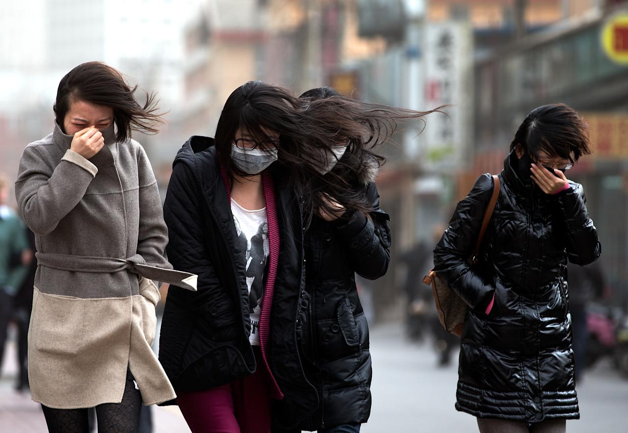 Chinese women, some wearing face masks, brace through strong wind after the capital city is hit by sandstorm in Beijing Thursday, Feb. 28, 2013. (AP Photo/Andy Wong)