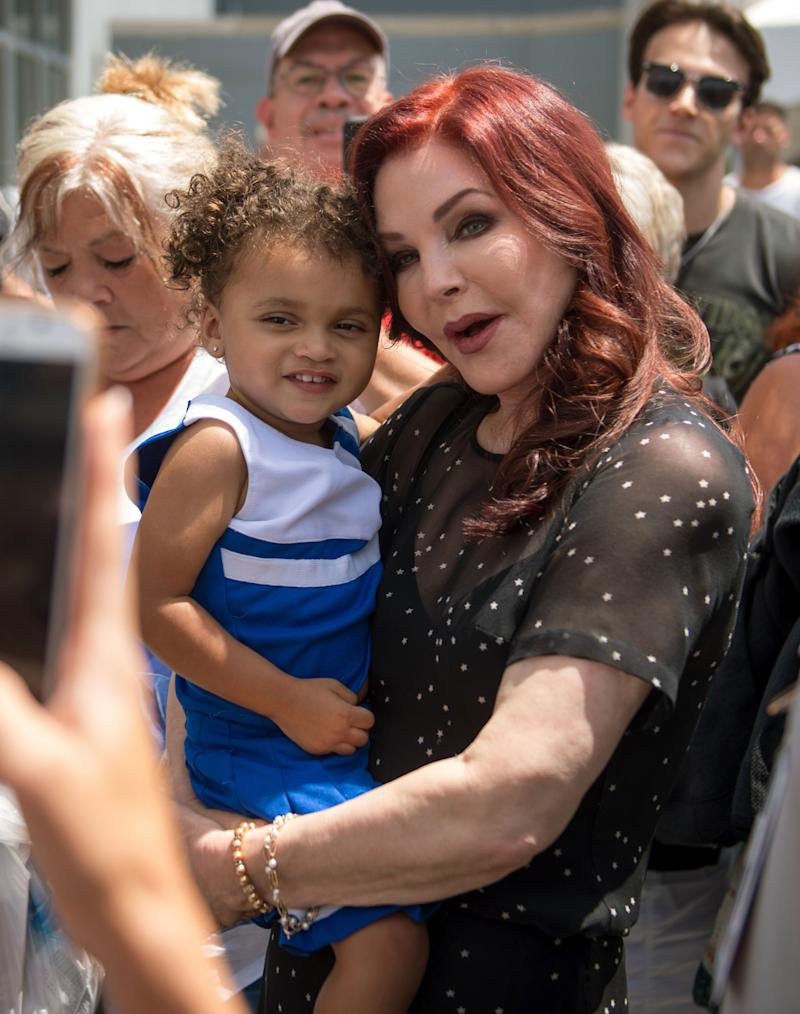 Priscilla Presley holds a child while greeting fans at Graceland