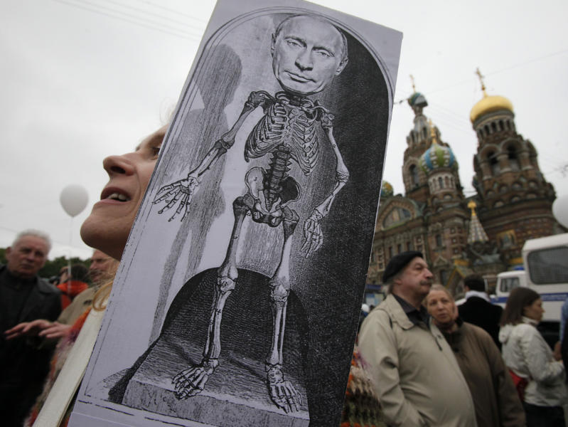 FILE - In this Tuesday, June 12, 2012 file photo, a woman holds a caricature depicting Russian President Vladimir Putin during an opposition rally 'For Russia without Putin!' in St. Petersburg, Russia. An Associated Press-GfK poll has shown that 60 percent of Russians still maintain a favorable opinion of Putin, despite rising opposition to him in Moscow, where tens of thousands have come out onto the streets in protest. (AP Photo/Dmitry Lovetsky, file)