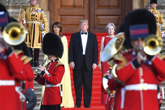 <p>Britain's Prime Minister Theresa May, right, stands with President Donald Trump, centre, and first lady Melania Trump on the steps of the Great Court as the bands of the Scots, Irish and Welsh Guards perform a ceremonial welcome, as they arrive for a black-tie dinner at Blenheim Palace, at Blenheim, west of London, Thursday July 12, 2018. (Photo: Ben Stansall / Pool via AP) </p>