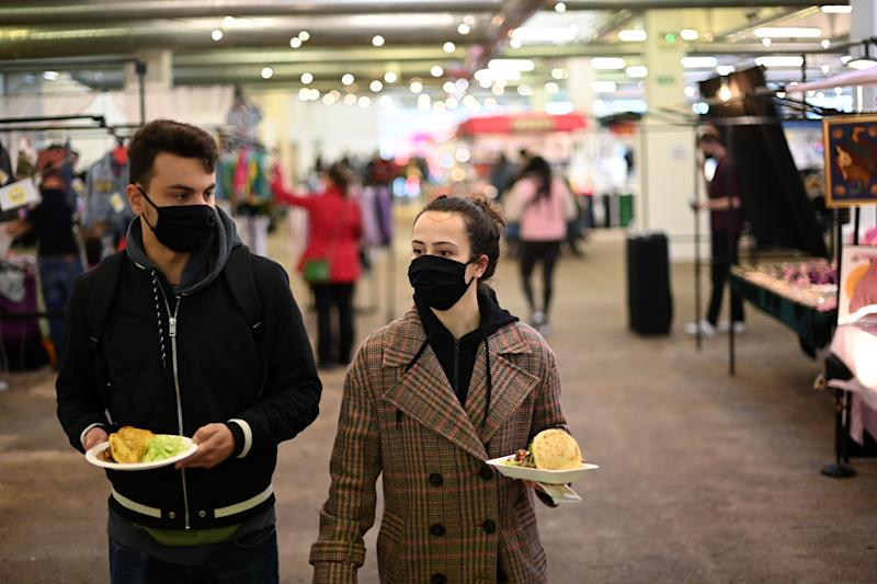 People wearing protective face masks looks for a seat to eat their lunch in The Old Truman Brewery's markets in east London on September 26, 2020, as Londoners live with new restrictions, introduced to combat the spread of the novel coronavirus pandemic. - Britain has tightened restrictions to stem a surge of coronavirus cases, ordering pubs to close early and advising people to go back to working from home to prevent a second national lockdown. (Photo by DANIEL LEAL-OLIVAS / AFP) (Photo by DANIEL LEAL-OLIVAS/AFP via Getty Images)