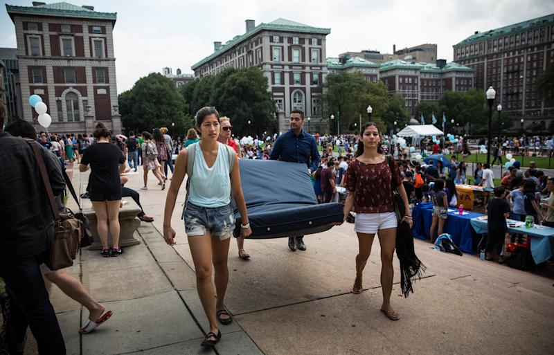 Emma Sulkowicz carries a mattress, with the help of three strangers who met her moments before, in protest of the university's lack of action after she reported being raped during her sophomore year at Columbia. (Andrew Burton via Getty Images)