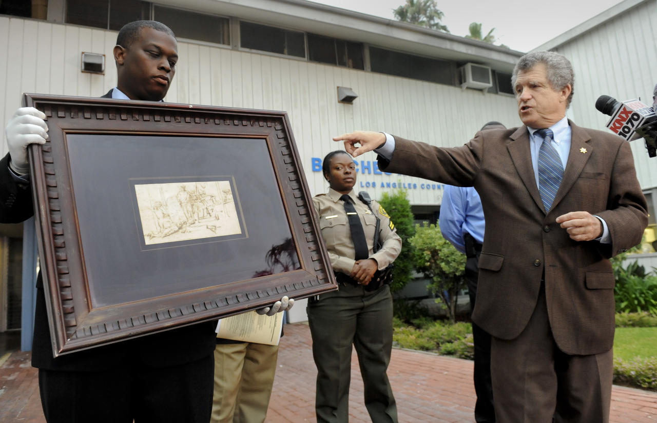 "Los Angeles Sheriff lead detective Clarence Williams, left, and Los Angeles County sheriff's spokesman Steve Whitmore, right, display the recovered $250,000 quill pen Rembrandt drawing known as ""The Judgment"" at a news conference, Tuesday, Aug. 16, 2011, in Marina Del Rey, Calif. Authorities said early Tuesday they had recovered the Dutch master's 17th century sketch at a San Fernando Valley church, about 20 miles from the luxury hotel lobby where it was stolen over the weekend from a private art display while a curator was momentarily distracted by someone who seemed interested in buying another piece. (AP Photo/Gus Ruelas)"