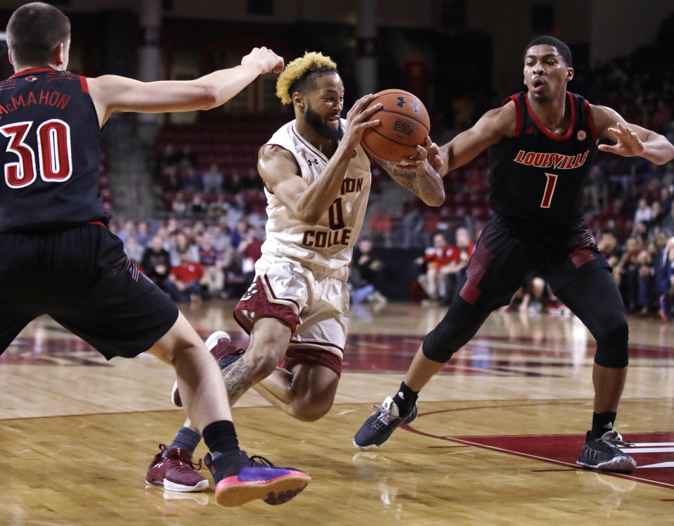 Boston College guard Ky Bowman, center, threads between Louisville's Ryan McMahon, left, and Christen Cunningham, right, on a drive to the basket during the second half of an NCAA college basketball game in Boston, Wednesday, Feb. 27, 2019. (AP Photo/Charles Krupa)