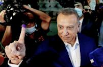Iraq's Prime Minister Mustafa Al-Kadhemi raises his ink-stained finger after casting his vote at a polling station in the capital Baghdad (AFP/-)