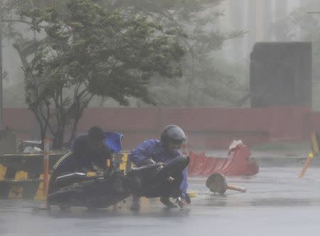 A man assisted a motorcyclist after he fell along a main road after strong winds brought by Typhoon Rammasun, locally called Glenda, battered the capital, metro Manila July 16, 2014. REUTERS/Romeo Ranoco