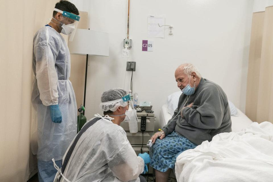 A physical therapist talks with a COVID-19 patient in Cranston, Rhode Island.