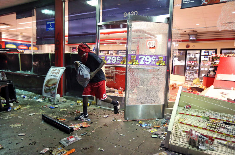 FILE - In this Aug. 10, 2014, file photo, a man loots a store in Ferguson, Mo. After a candlelight vigil, people protesting Brown's death smashed car windows and carried away armloads of goods from stores. (David Carson/St. Louis Post-Dispatch via AP, File)