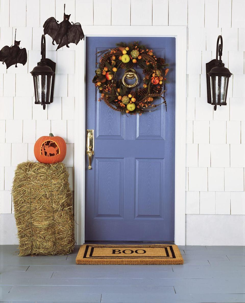 """<p>Even the DIY-phobic can make their porches a little more festive for trick-or-treaters by swapping in a new doormat and adding a <a href=""""https://www.countryliving.com/diy-crafts/g1988/fall-craft-projects/"""" rel=""""nofollow noopener"""" target=""""_blank"""" data-ylk=""""slk:fall wreath"""" class=""""link rapid-noclick-resp"""">fall wreath</a>, a bale of hay, and some faux hanging bats. </p>"""