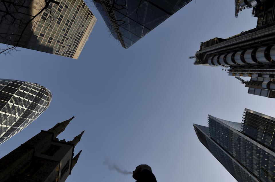 A city worker walks through the City of London with St. Andrew Undershaft church