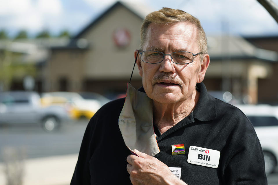In this Wednesday, May 19, 2021, photograph, Bill Easton, a checker at a Safeway grocery store, is shown in the shopping center in which the store is located in Aurora, Colo. Easton, like many other workers in retail sales jobs, is fully vaccinated but is concerned about risks posed as retailers change their mask-wearing policies for customers. (AP Photo/David Zalubowski)