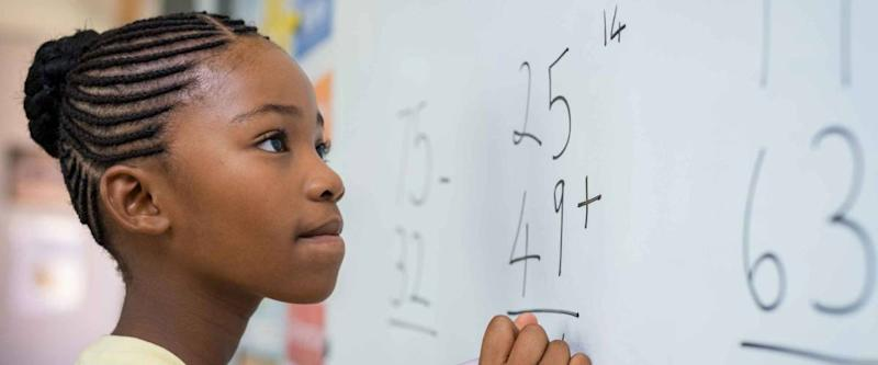 Portrait of Black girl writing solution of sums on white board at school.