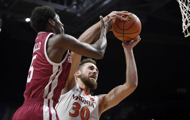 Virginia's Jay Huff, right, pulls down a rebound against Massachusetts' Samba Diallo during the first half of an NCAA college basketball game, Saturday, Nov. 23, 2019, in Uncasville, Conn. (AP Photo/Jessica Hill)
