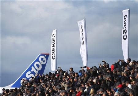 Bombardier employees and guests watch as the CSeries aircraft taxis past for its first test flight in Mirabel, Quebec, September 16, 2013. REUTERS/Christinne Muschi
