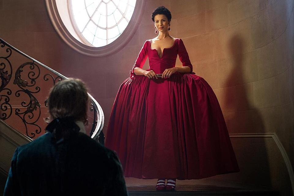 """<p><em>Outlander</em> costume designer Terry Dresbach knew the stakes were high when it came time for Caitriona Balfe to don Claire's red dress, a key moment in the second <em>Outlander</em> novel, <em>Dragonfly in Amber</em>. <a rel=""""nofollow"""" href=""""https://www.yahoo.com/tv/outlander-costume-designer-terry-dresbach-talks-020213539.html?soc_src=mail&soc_trk=ma"""" data-ylk=""""slk:As she told her husband;outcm:mb_qualified_link;_E:mb_qualified_link;ct:story;"""" class=""""link rapid-noclick-resp yahoo-link"""">As she told her husband</a> — and series showrunner — Ronald D. Moore, if they didn't get it absolutely right, fans would """"burn us at the stake."""" Fortunately for their continued survival, viewers' jaws dropped even further than Jamie's when Claire descended that staircase clad in resplendent red. Simply put, that dress is the hottest in haute couture. —<em>Ethan Alter</em> <br>(Photo: Starz) </p>"""